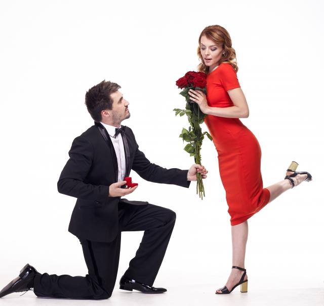 赤いドレスの女性に、花でプロポーズする男性